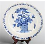 A late 18th century tin glazed Delftware charger, decorated with basket of flowers within a