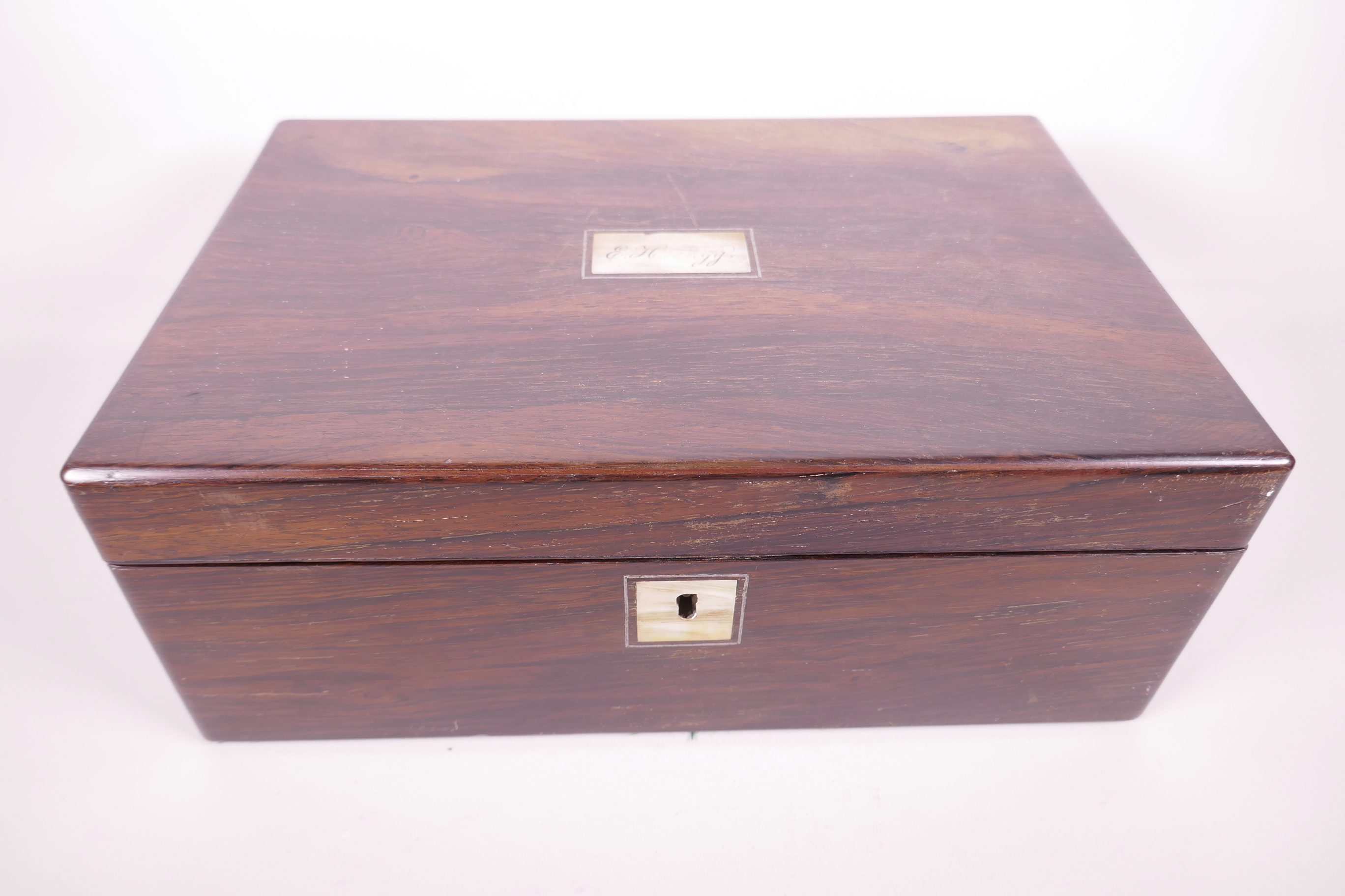 Lot 179 - A C19th rosewood writing slope, with mother of pearl plaque to lid, the fitted interior with two