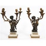 PAIRE DE CANDÉLABRES D'après Clodion représentant deux enfants en bronze patiné supportant quatre