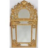 MIROIR EN BOIS DORE REGENCE A pare close, à miroir biseauté,en bois doré à motifs de baguettes à