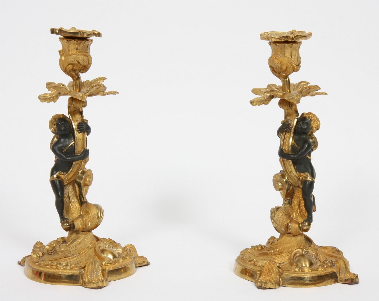 PAIRE DE BOUGEOIRS ROCAILLE AUX CHERUBINS En bronze à patine brune et dorée, de style Rocaille à