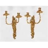 PAIRE D'APPLIQUES REGENCE  En bronze doré à deux bras de lumière asymétriques supportant un bassin