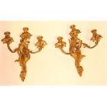 PAIRE D APPLIQUES LOUIS XV  A trois bras de lumière entrelacés sur un fût à mouvement rocaille.