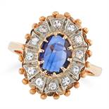 A SAPPHIRE AND DIAMOND CLUSTER RING set with an oval rose cut sapphire in a cluster of round