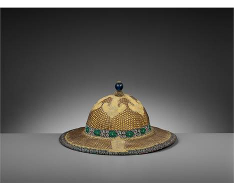 AN OFFICIAL'S SUN HELMET, QING DYNASTYChina, 1644-1912. Silk, gold thread, gilt metal, and rattan. Shaped as a pith or sun he