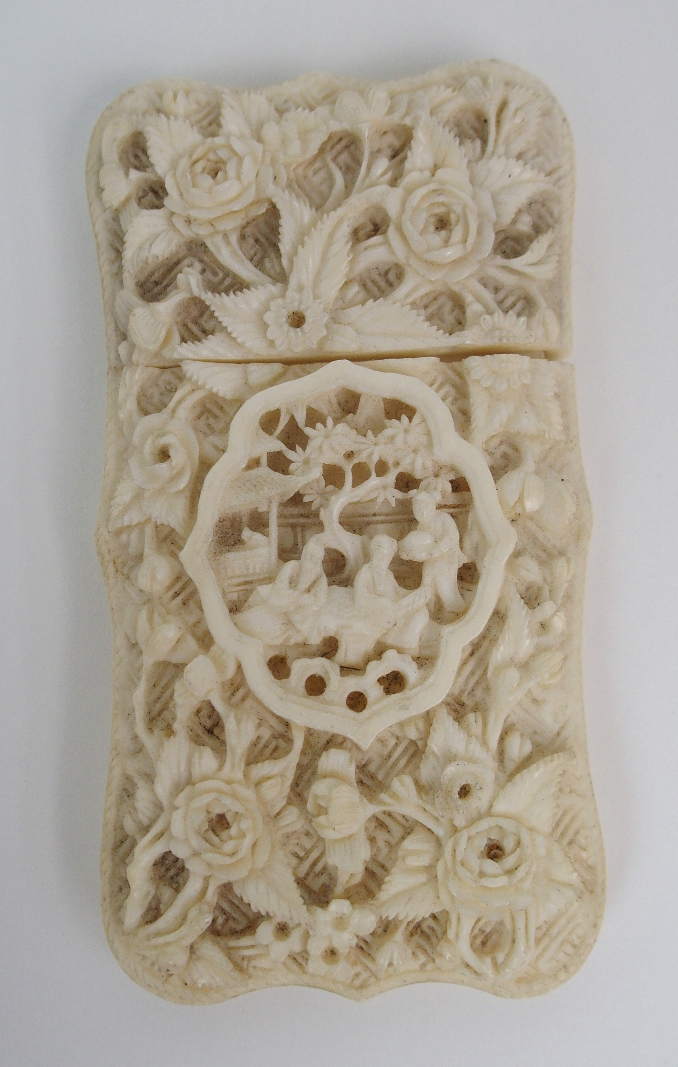 Lot 26 - A CANTONESE IVORY CARD CASE carved allover with a vignette of figures amongst foliage, 8.5cm high, a
