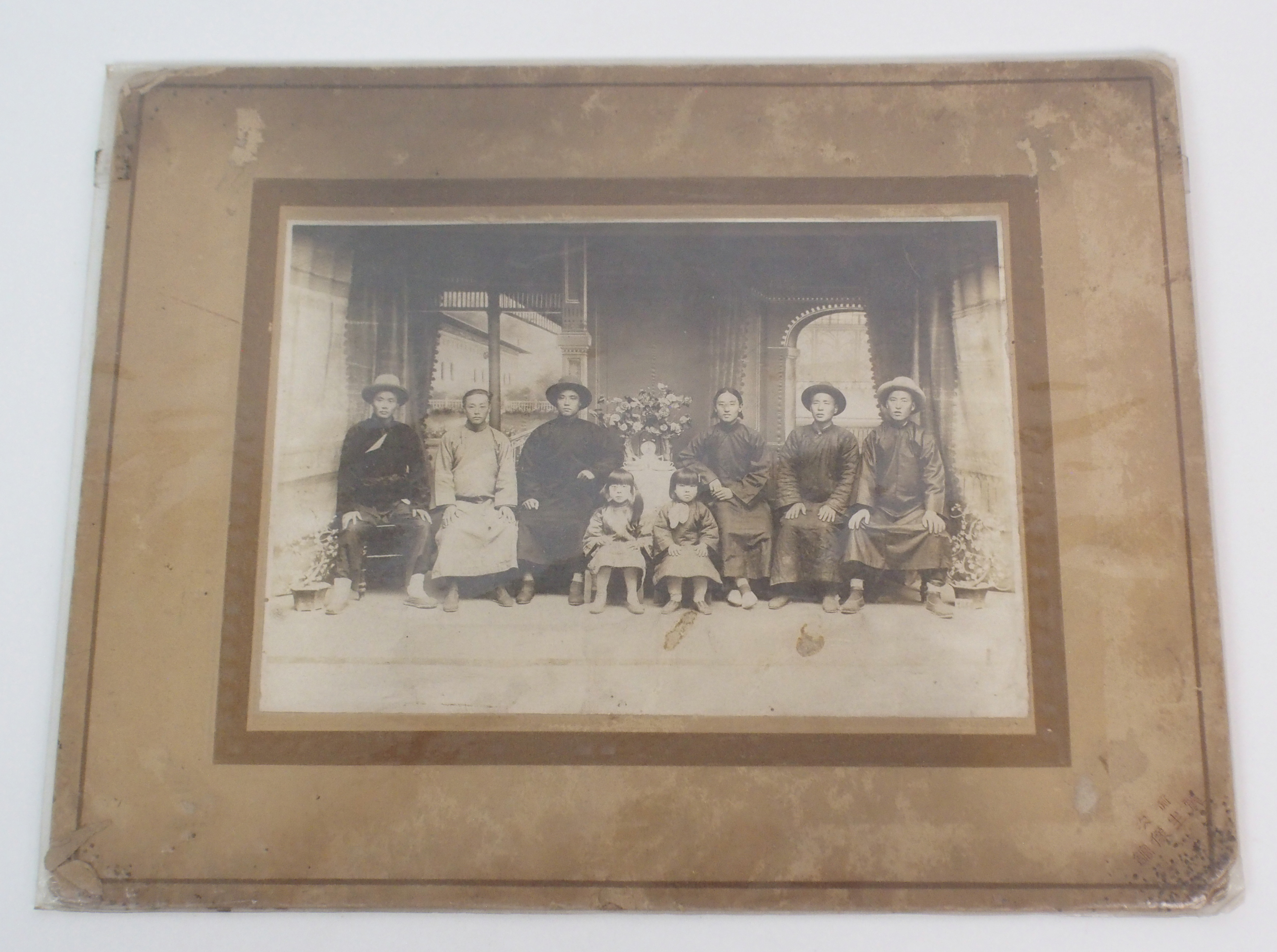 Lot 60 - A CHINESE PHOTOGRAPH OF A FAMILY GROUP with eight adults and two children in an interior, 14cm x