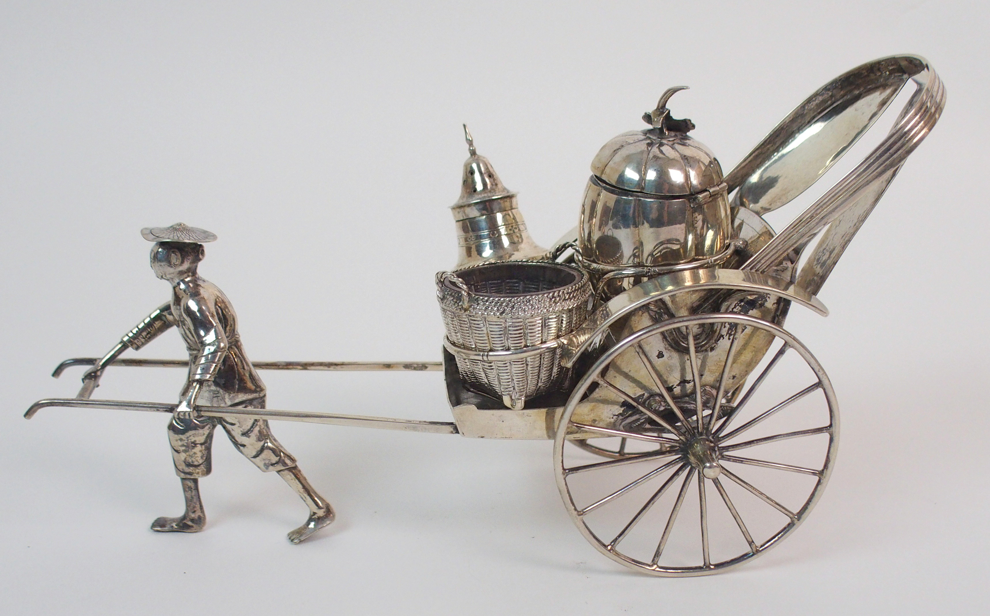 Lot 47 - A CHINESE SILVER RICKSHAW CRUET of traditional type with salt, pepper and mustard pot, the carriage,