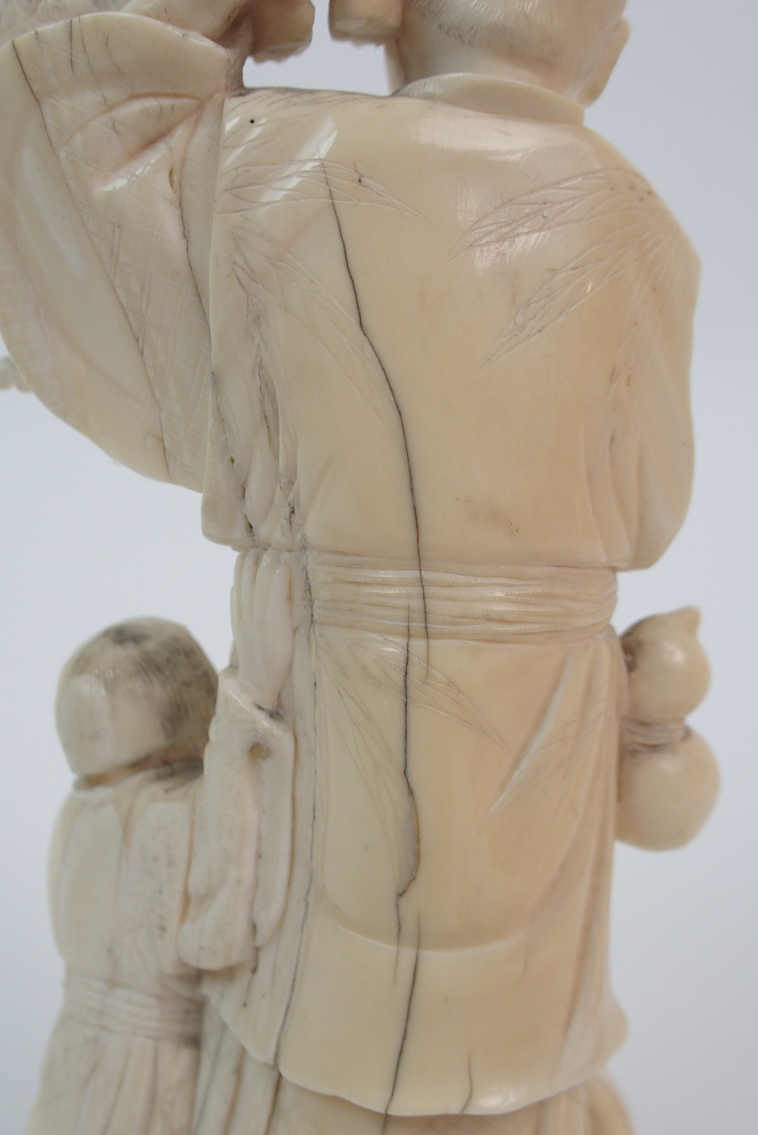 Lot 42 - A JAPANESE IVORY OKIMONO carved with a man holding two Oni above a child beating a drum (with some