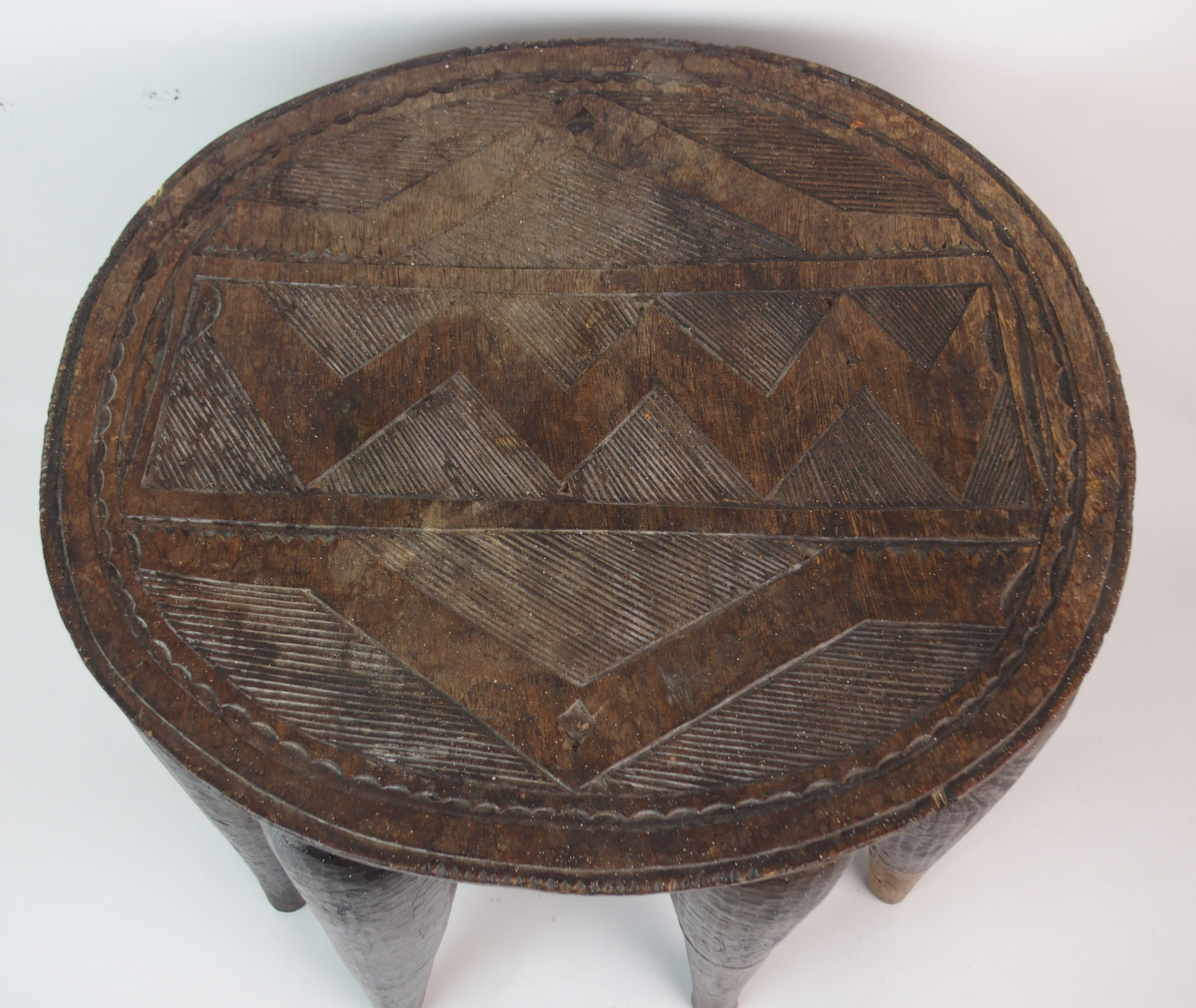 Lot 29 - AN AFRICAN HARDWOOD CIRCULAR STOOL the seat carved with geometric patterns and on ten tapering
