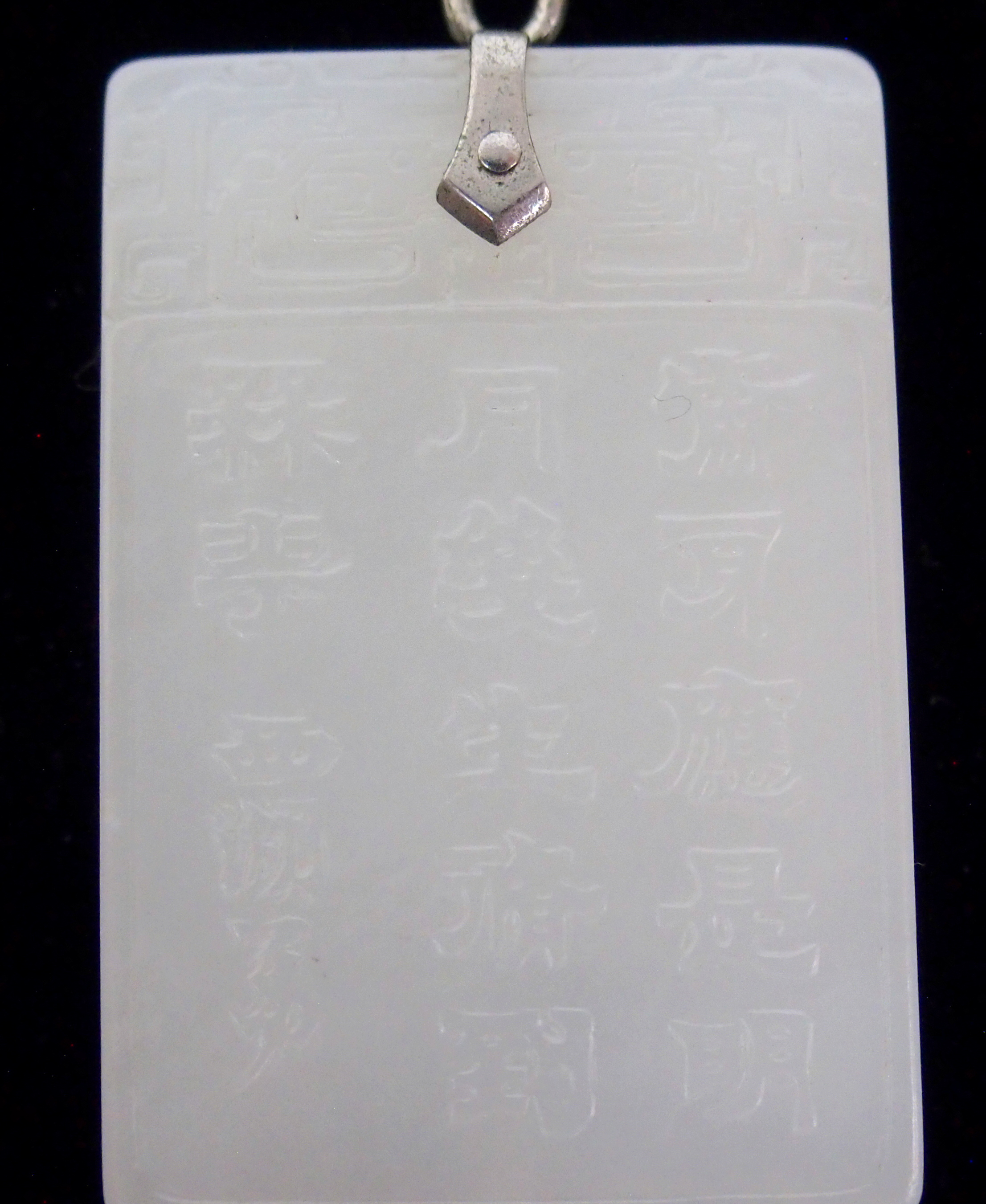 Lot 31 - A CHINESE JADE RECTANGULAR PENDANT carved to one side with a figure of Guanjin, the other side