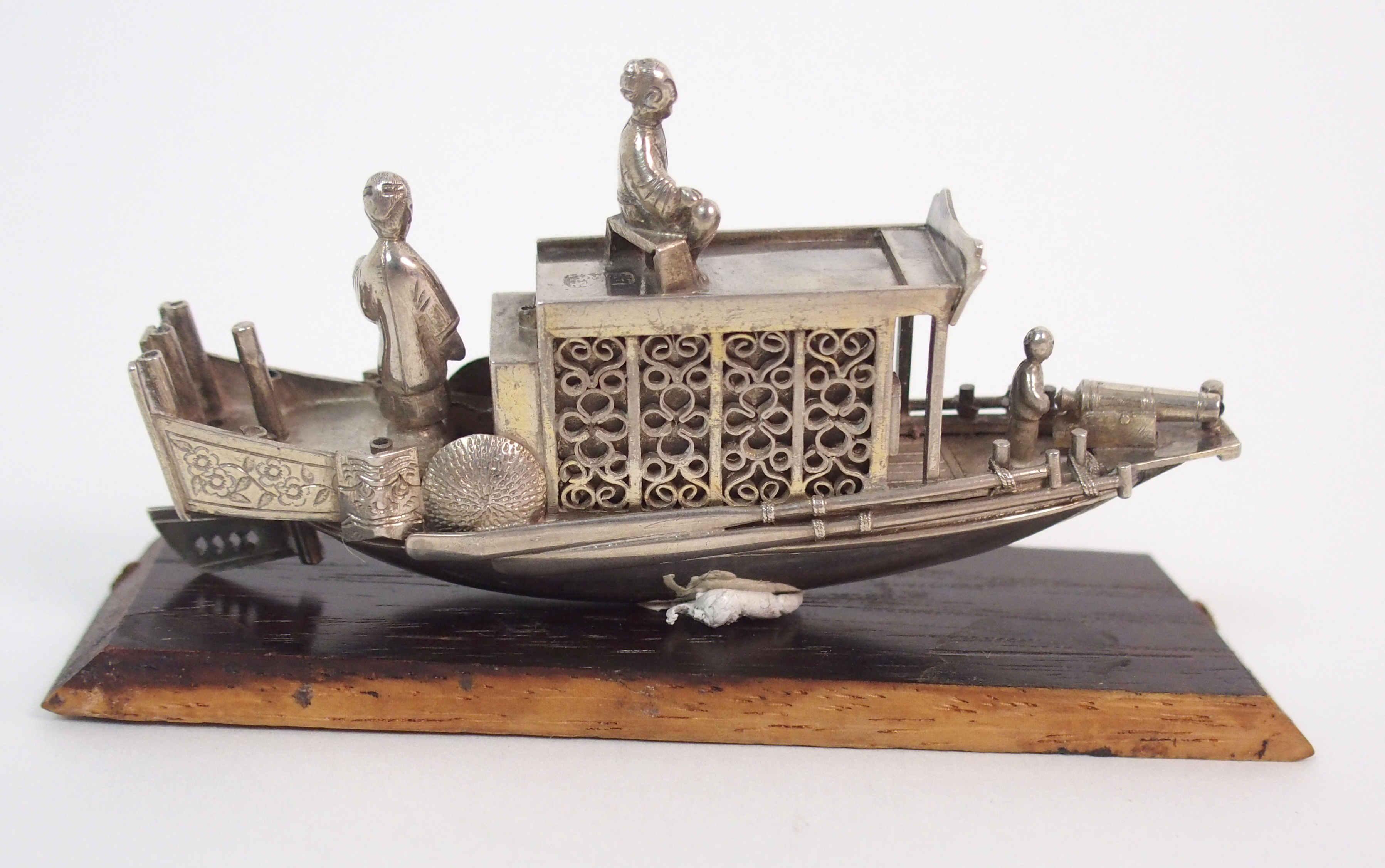 Lot 48 - A CHINESE WHITE METAL JUNK of traditional type, 8.5cm wide, wood base, 51 grams overall weight and