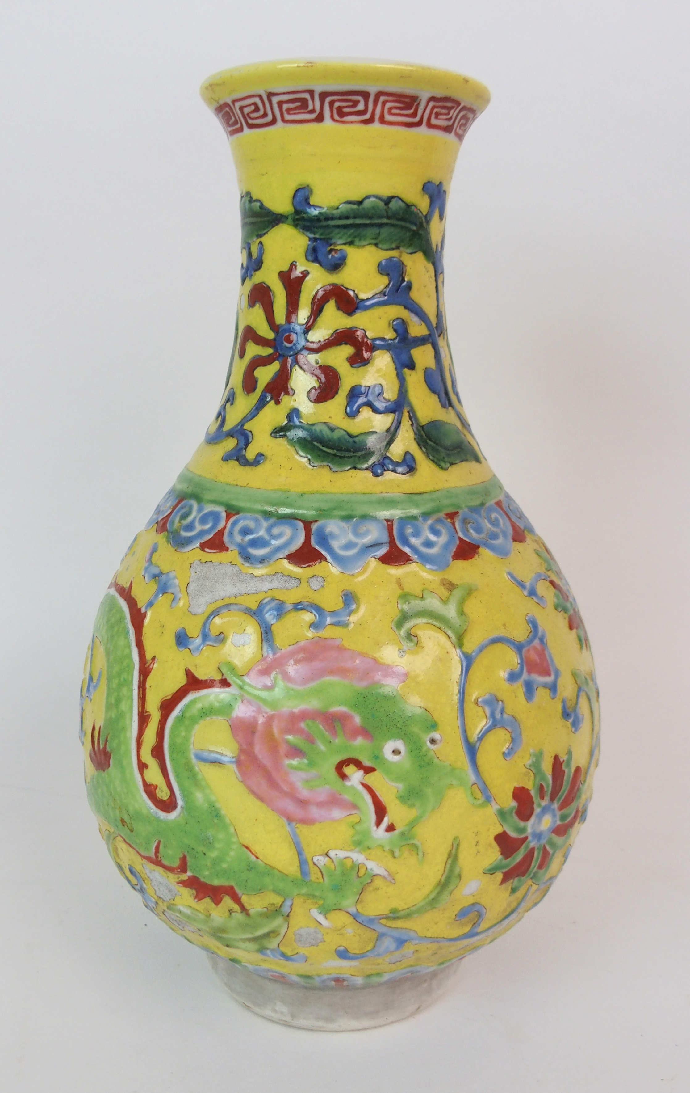 Lot 23 - A CHINESE RELIEF MOULDED BALUSTER VASE decorated with dragons and foliage on a yellow ground (