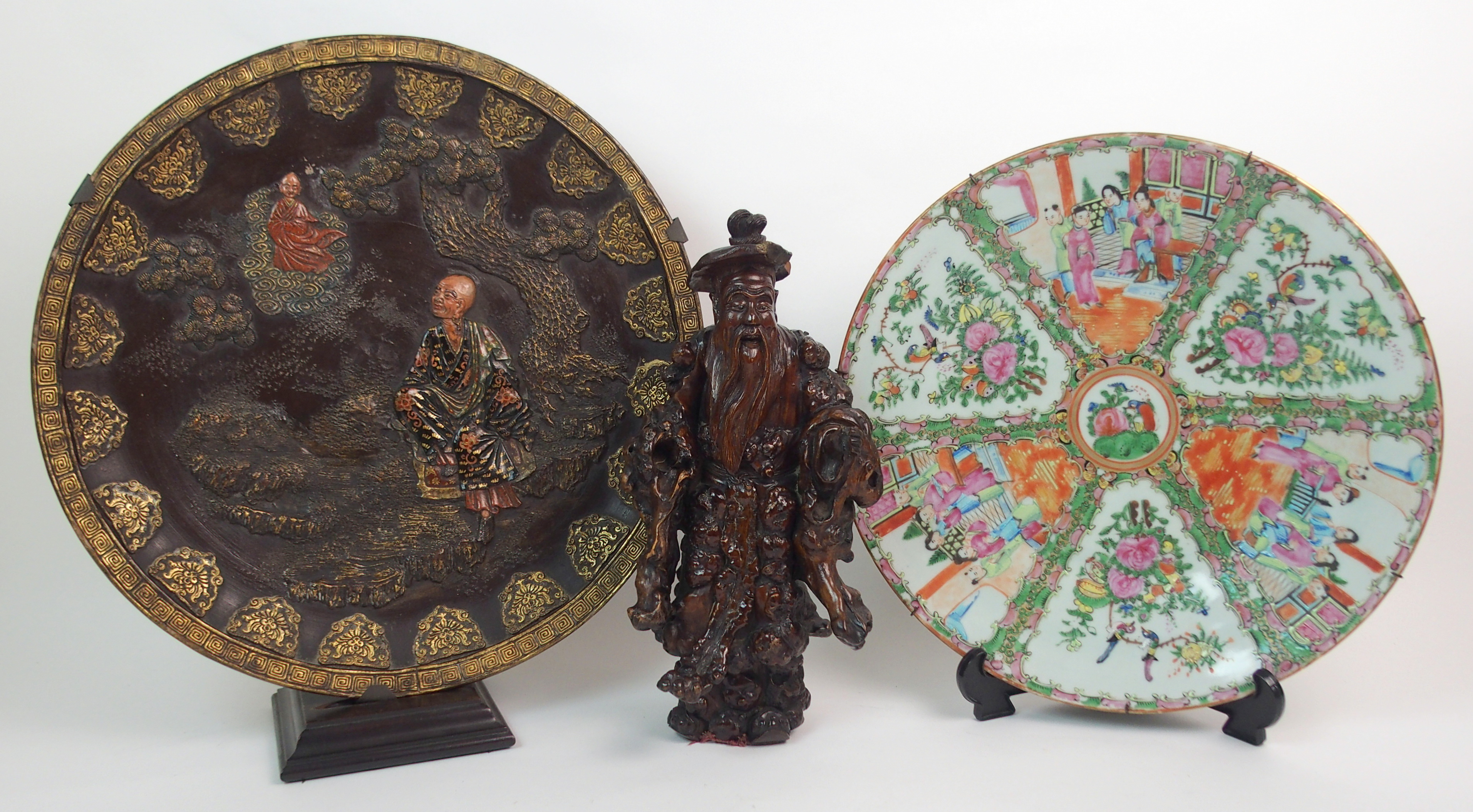 Lot 40 - A JAPANESE POTTERY DISH in the Komai style moulded with a deity and devotee amongst pine (rim