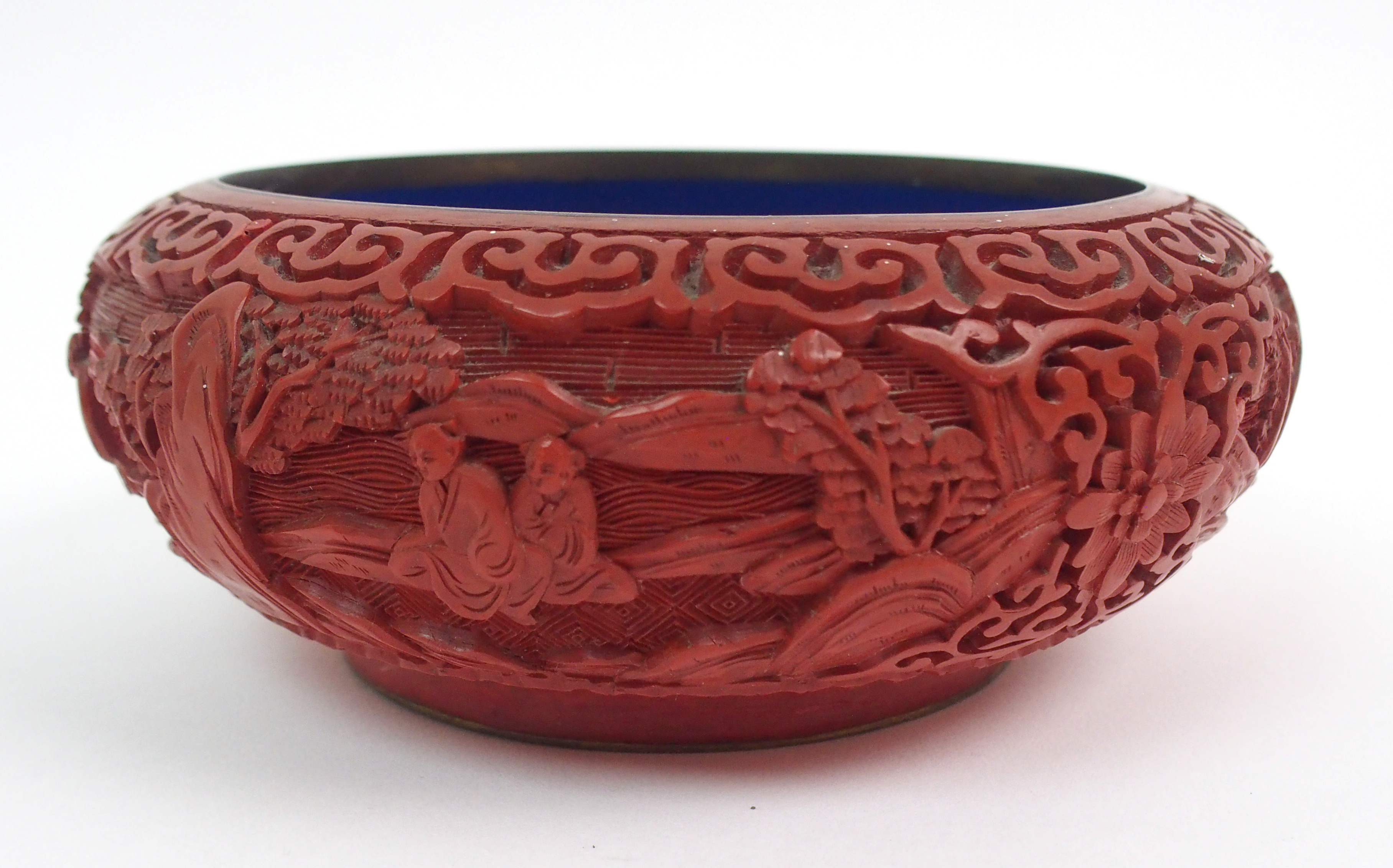 Lot 39 - A CHINESE CINNABAR BOWL carved with figures resting in gardens divided by lotus and within stiff