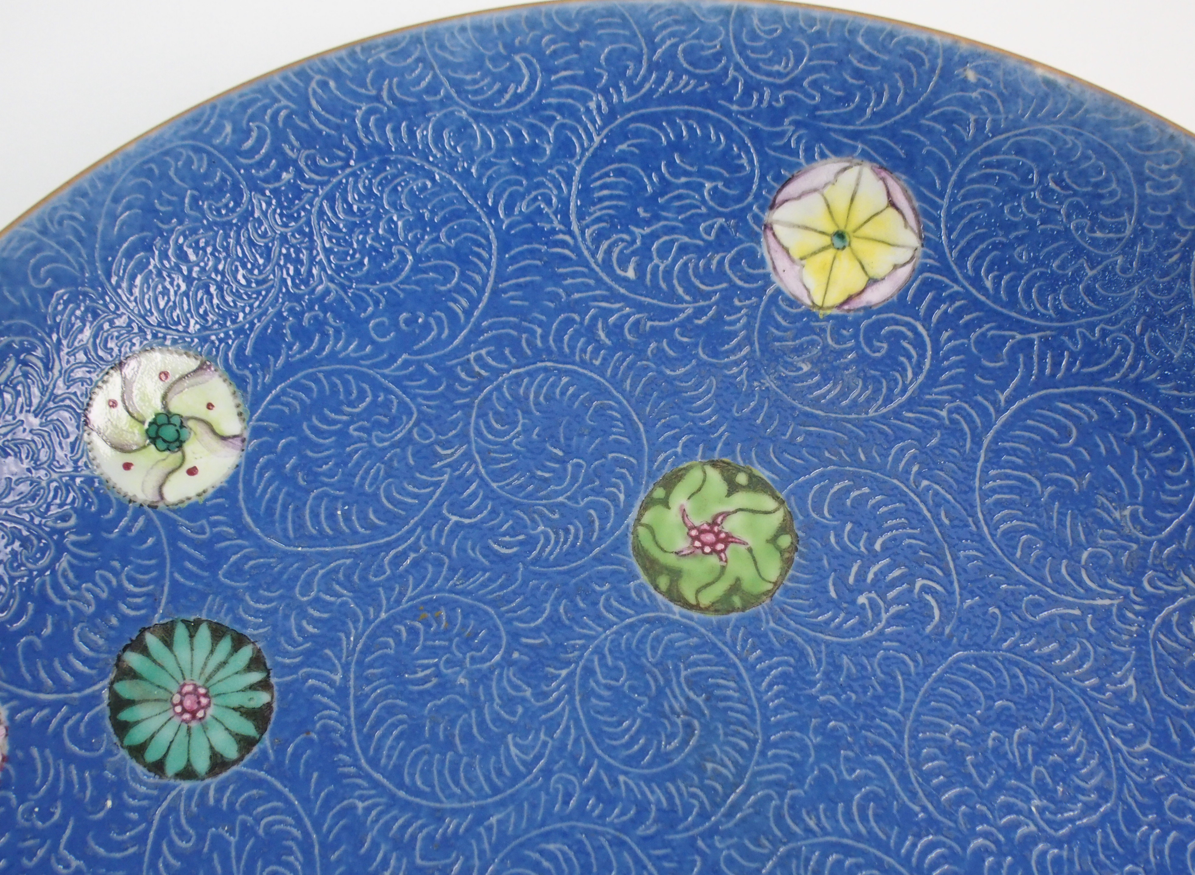 Lot 45 - A CHINESE PORCELAIN DISH with incised scrolling and enamel foliage on a blue ground, blue seal mark,
