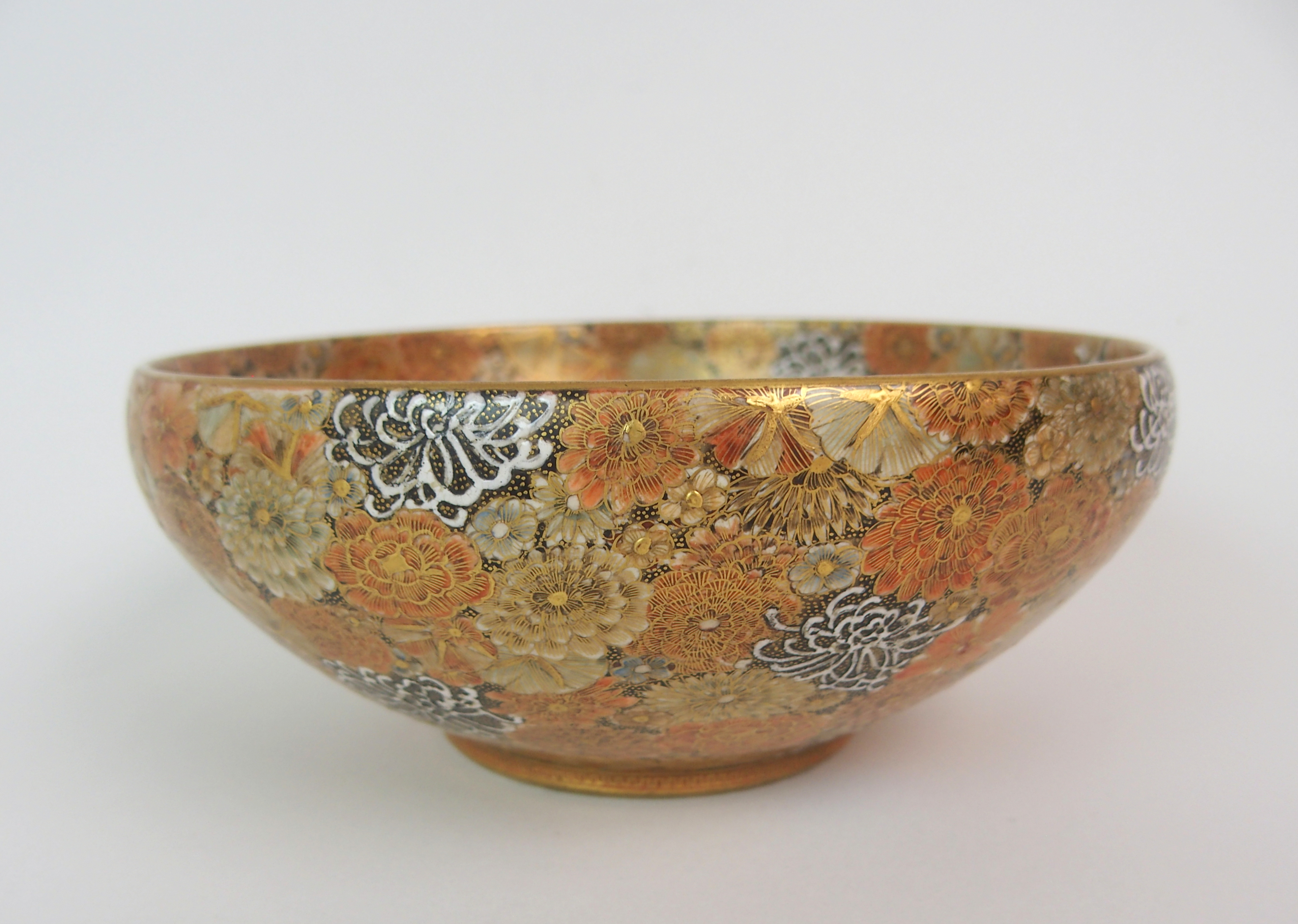 Lot 20 - A SATSUMA BOWL painted allover with dense flowers in various enamel colours, gilt dentil foot rim,