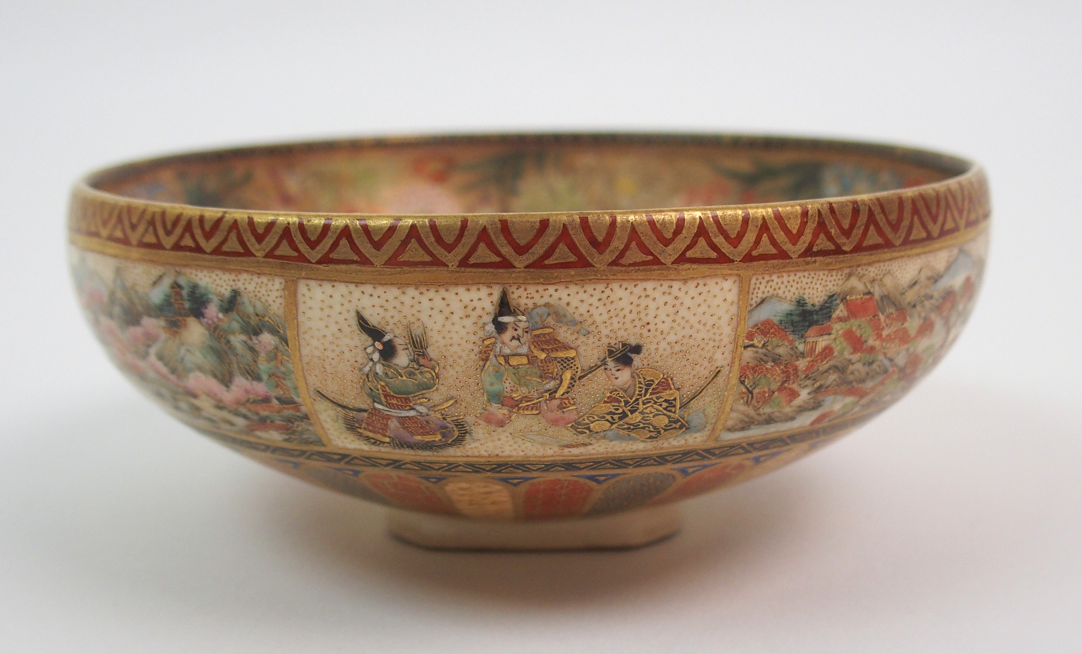 Lot 37 - A SATSUMA BOWL painted with panels of figures, landscapes and flowers above a stiff leaf band,