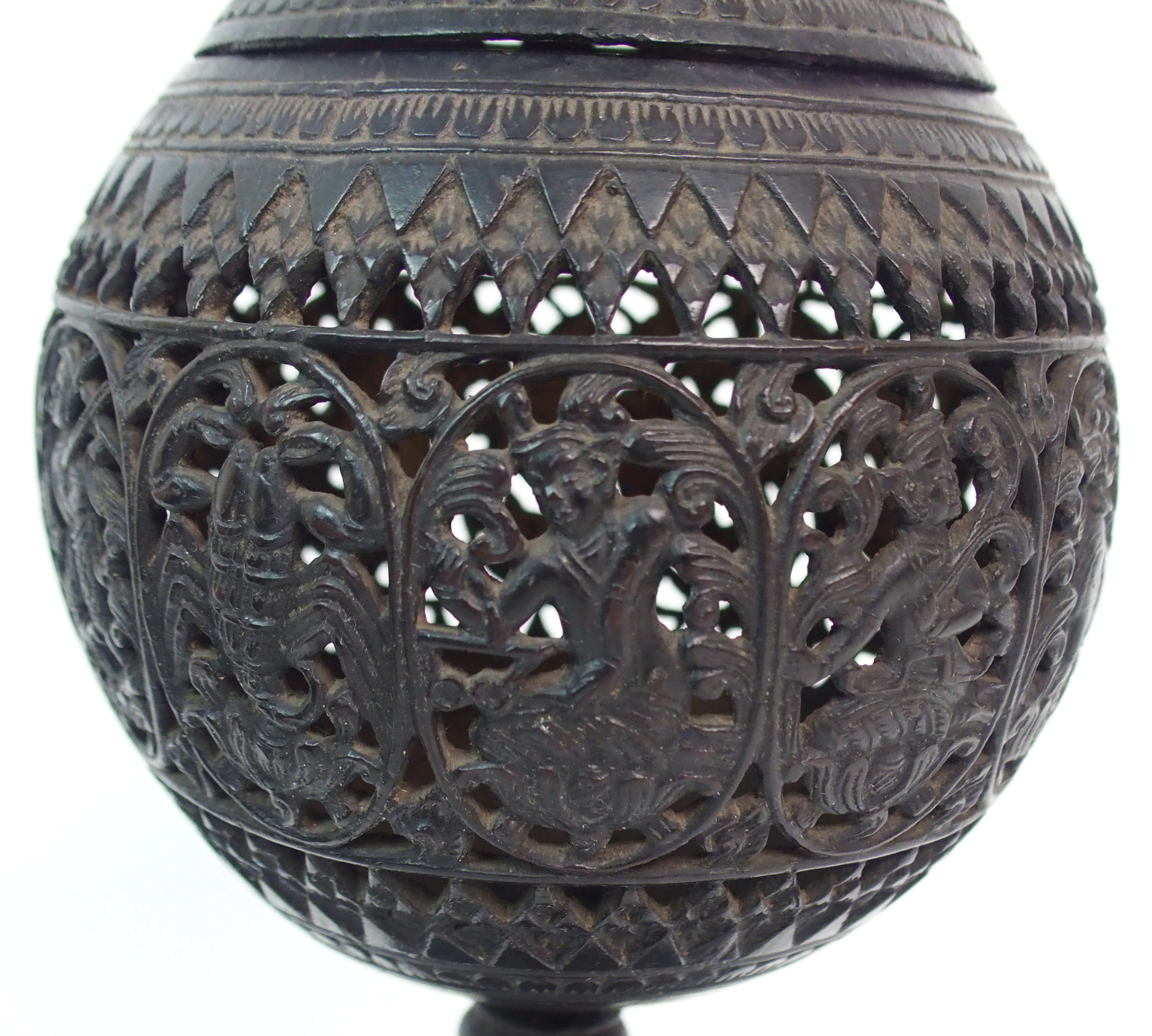 Lot 52 - A BURMESE CARVED COCONUT, COVER AND STAND pierced with panels of zodiacal design and stiff leaves (