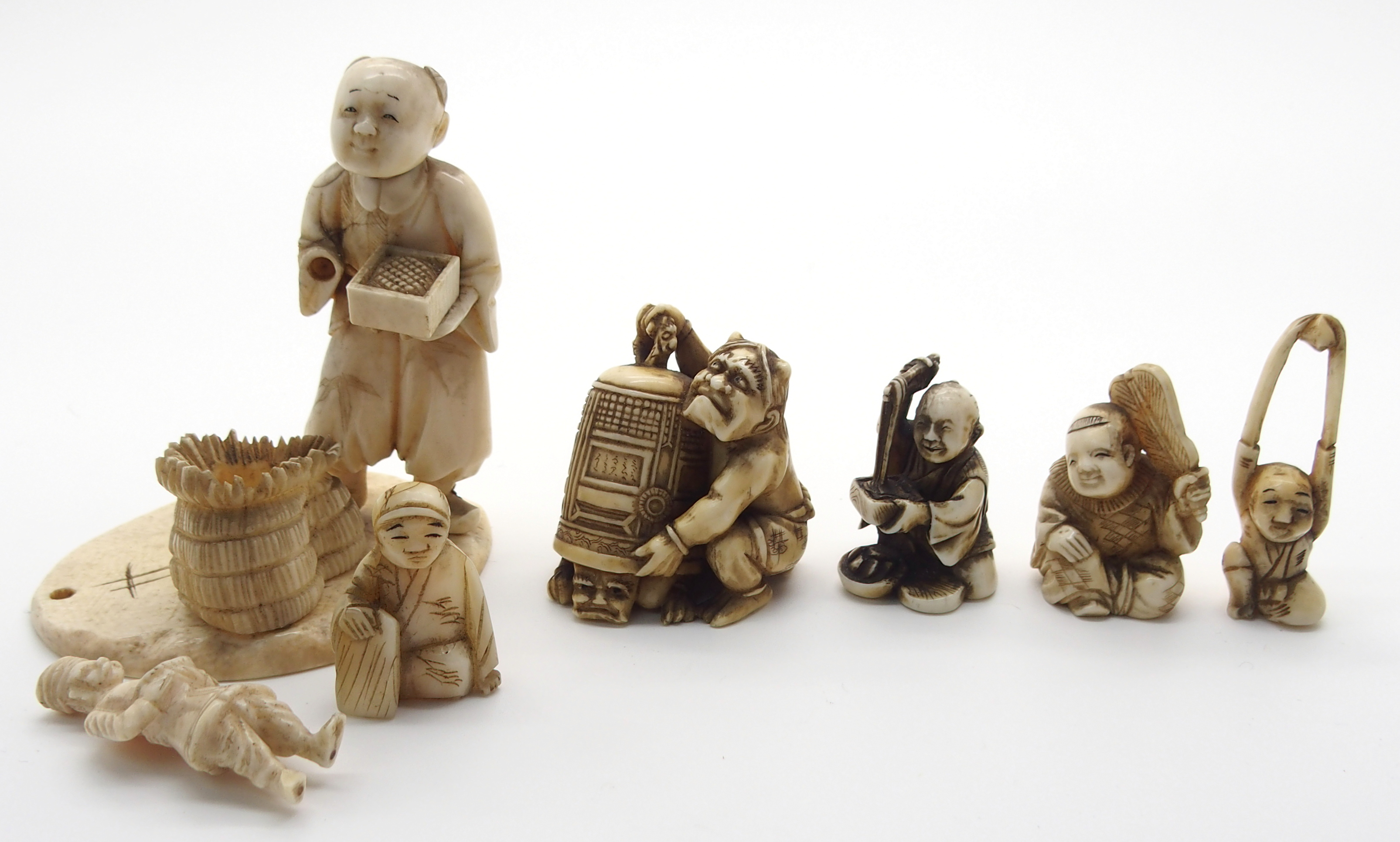 Lot 7 - A JAPANESE IVORY OKIMONO ONI holding a temple bell enclosing another demon, 5cm high, a netsuke of a