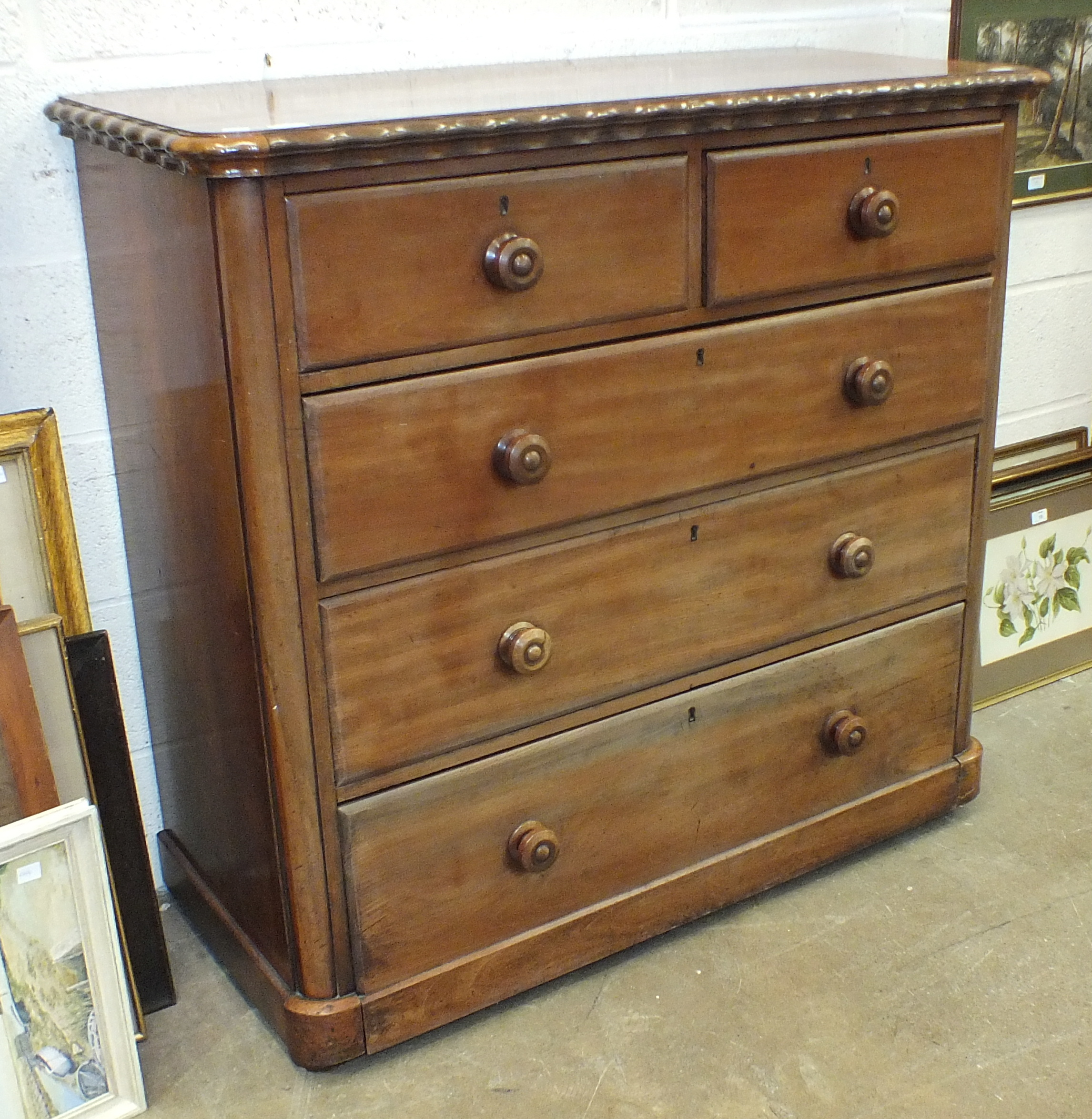 A mahogany finish straight-front chest, the rectangular top with wavy edge above two small and three