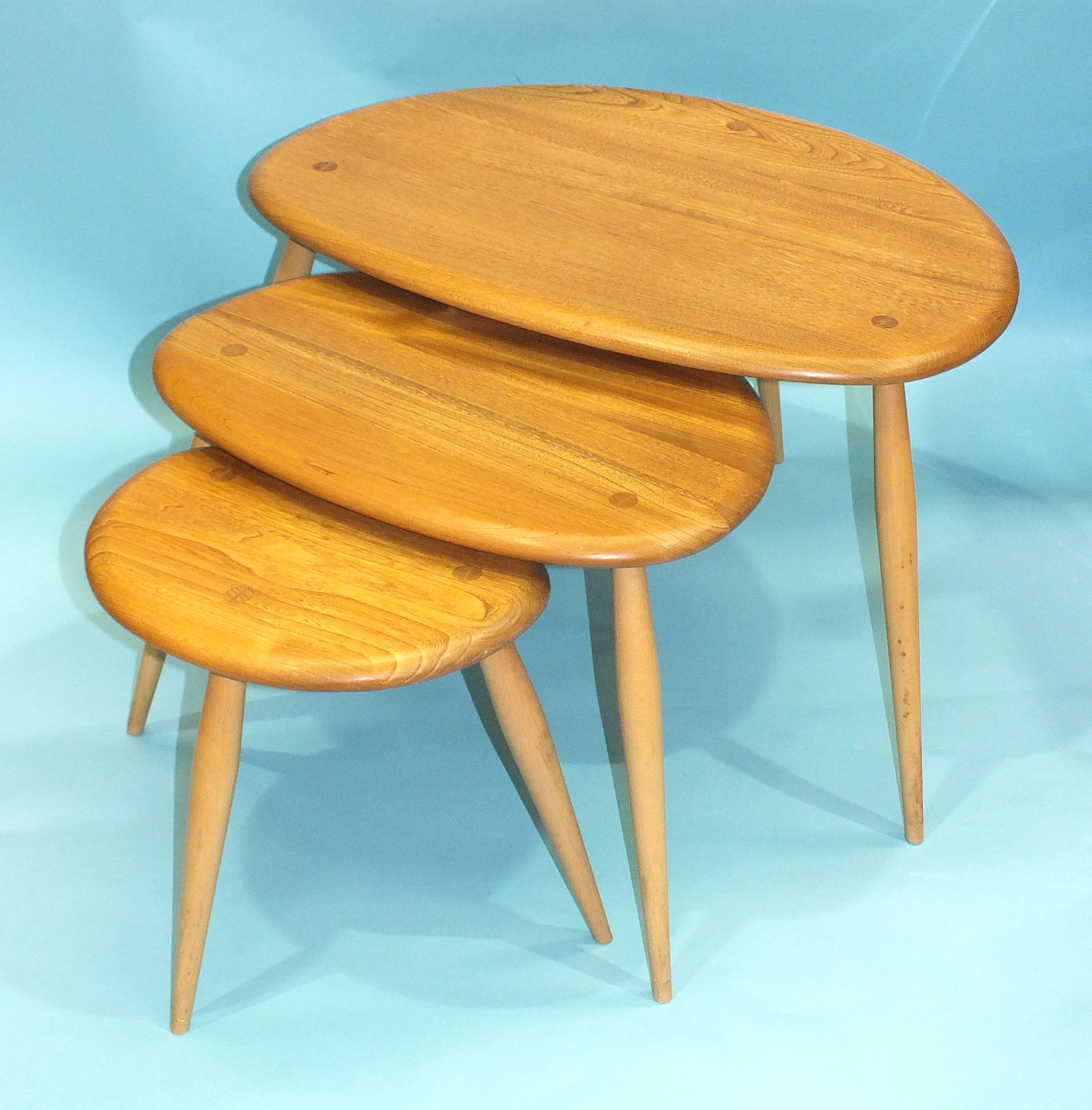 An Ercol nest of three light elm and beech 'Pebble' tables, largest 64cm wide, 41cm high.
