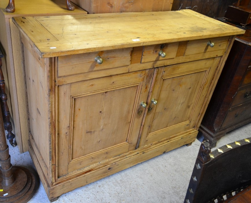 Lot 56 - Antique waxed pine dresser base with three drawers over panelled cupboard doors