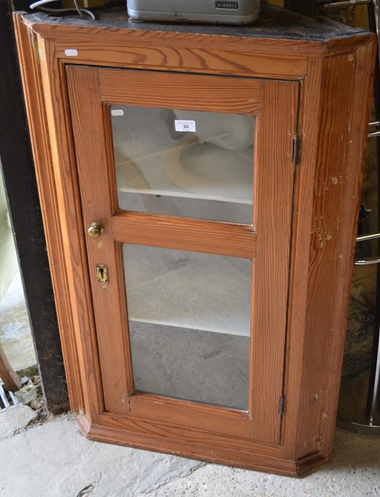 Lot 30 - A stained pine hanging corner cupboard with single glazed door enclosing two shelves