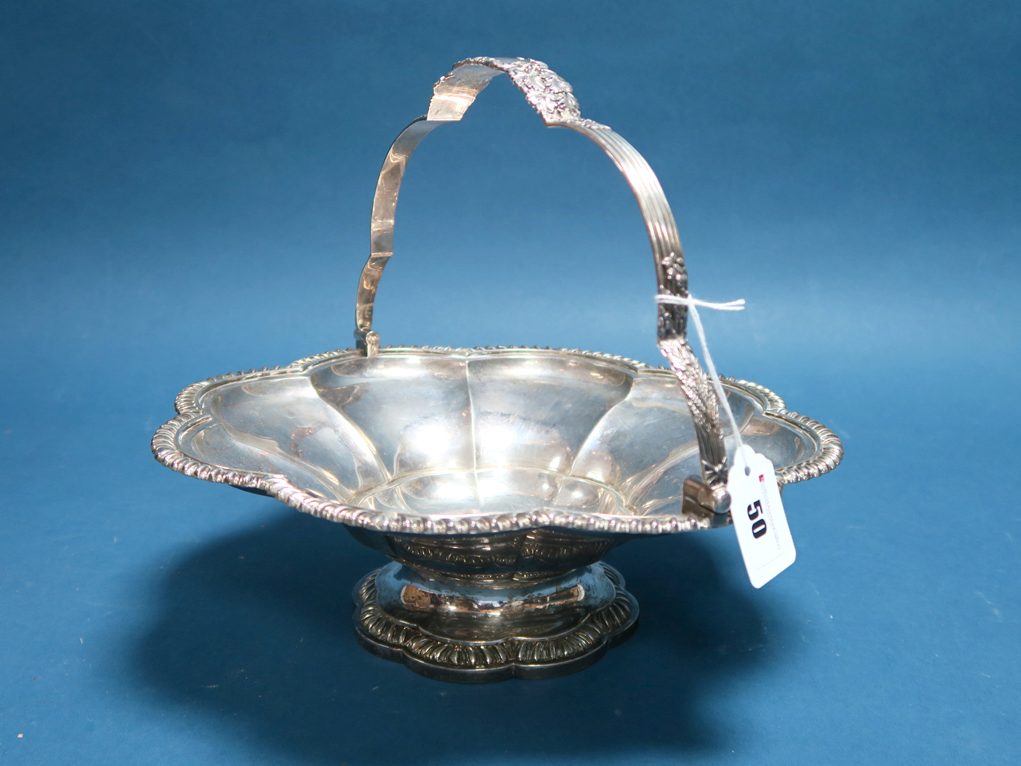 Lot 50 - A Large Georgian Hallmarked Silver Swing Handled Basket Dish, (makers mark rubbed) London 1820, of