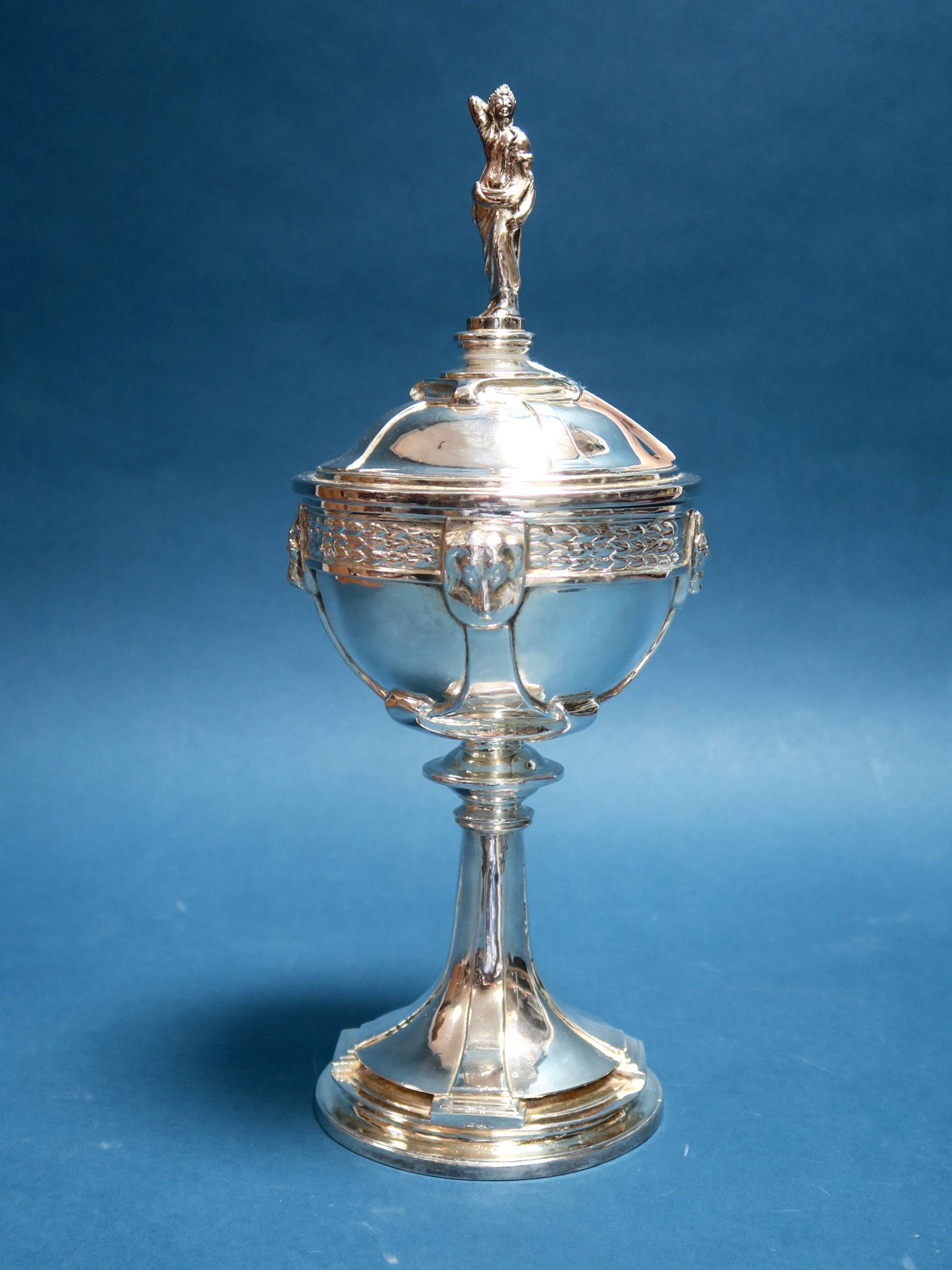 Lot 4 - An Arts & Crafts Style Lidded Trophy Cup and Cover, detailed with wild animal masks, the circular