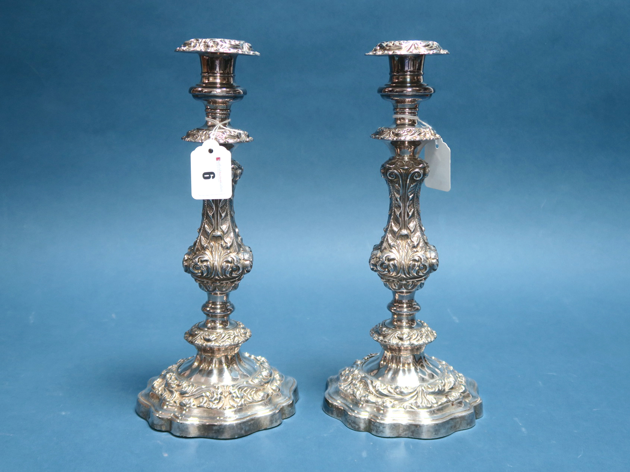 Lot 6 - A Highly Decorative Pair of Plated Candlesticks, each shaped circular base supporting square