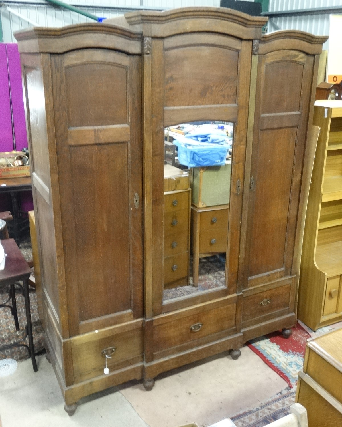 Lot 51 - A late 19th / early 20th C oak breakfront triple armoire/ bibliotech with a mirror central door and