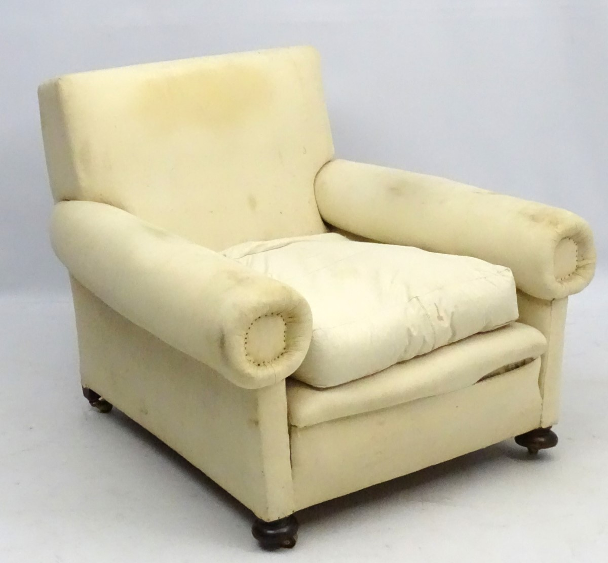 Lot 9 - A late Victorian upholstered and overstuffed armchair with walnut bun feet.