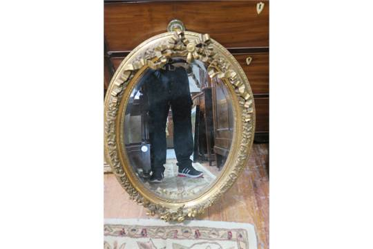 A Victorian Style Oval Framed Mirror The Foliate Frame Decorated