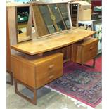 A retro G-Plan triple-mirrored light teak dressing table fitted with two drawers and a cupboard