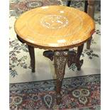 An Indian hardwood circular-top table with inlaid decoration, on three elephant mask supports,