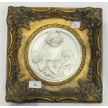 A pair of circular plaster wall plaques decorated in relief with putti, 16cm diameter, within gilt