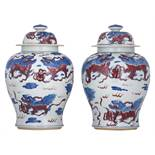 A pair of Chinese cobalt blue and copper-red vases and covers, decorated with kylins, H 49 cm