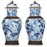 A pair of Chinese blue and white stoneware vases and covers, decorated with flowers and birds, marke