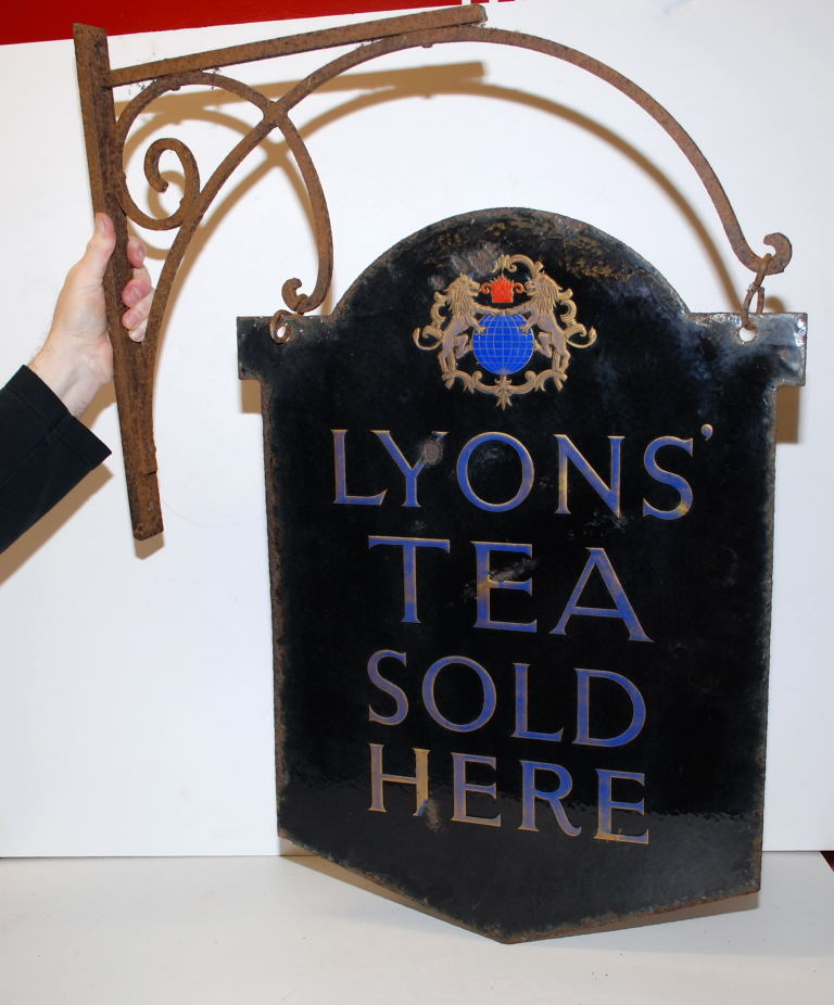 """Lot 23 - ENAMELLED SIGN """"LYON'S TEA SOLD HERE"""" COMPLETE WITH HANGING WALL BRACKET  HT."""