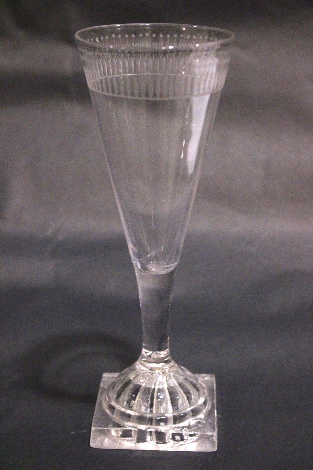 """A TAPERED GLASS FLUTE, with cut detail to the rim, raised on a lemon squeeze foot / base, 7"""" tall"""