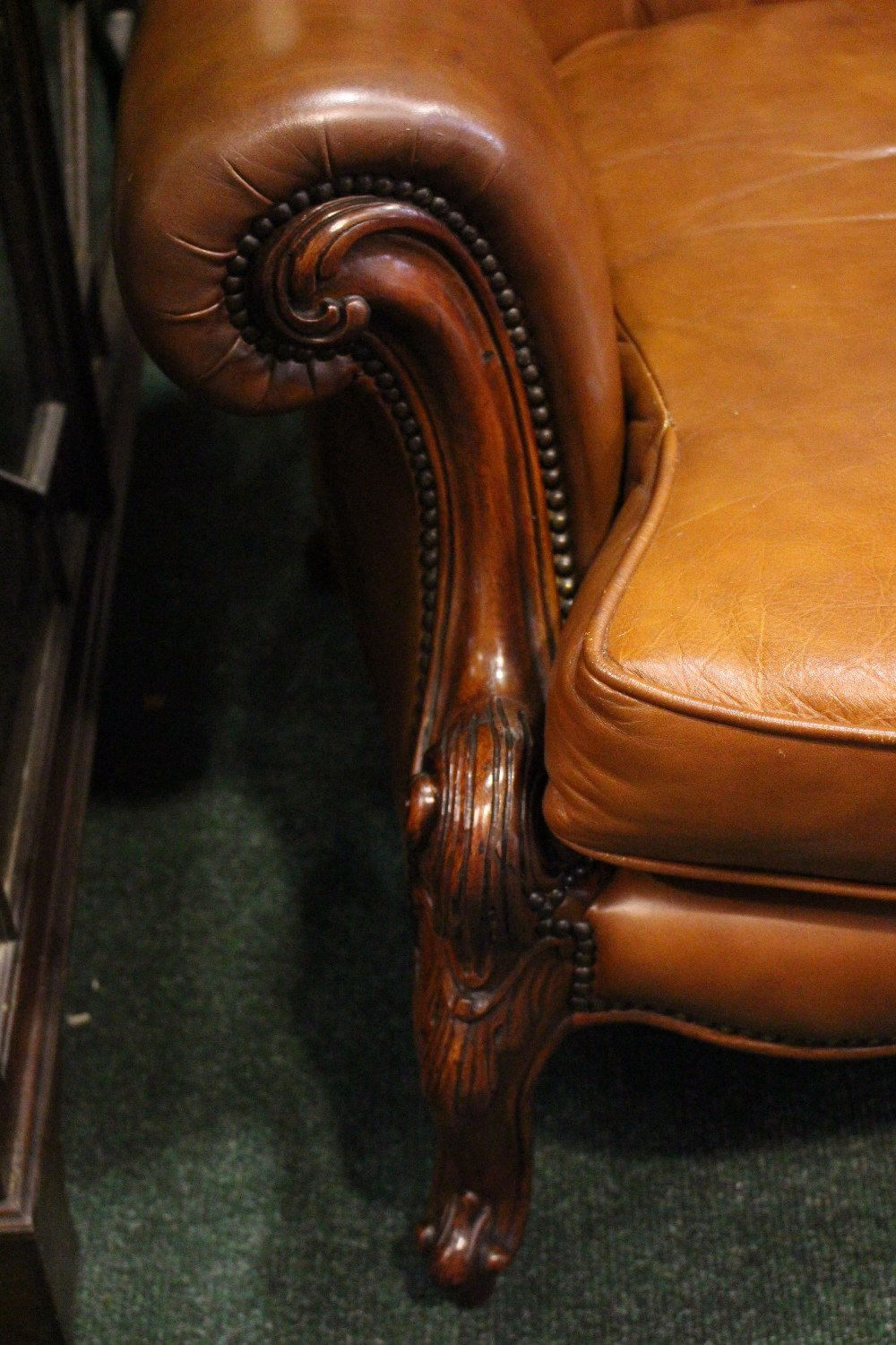 Lot 28 - A PAIR OF TAN COLOURED LEATHER WING BACK ARMCHAIRS, button backs, raised on carved cabriole legs,
