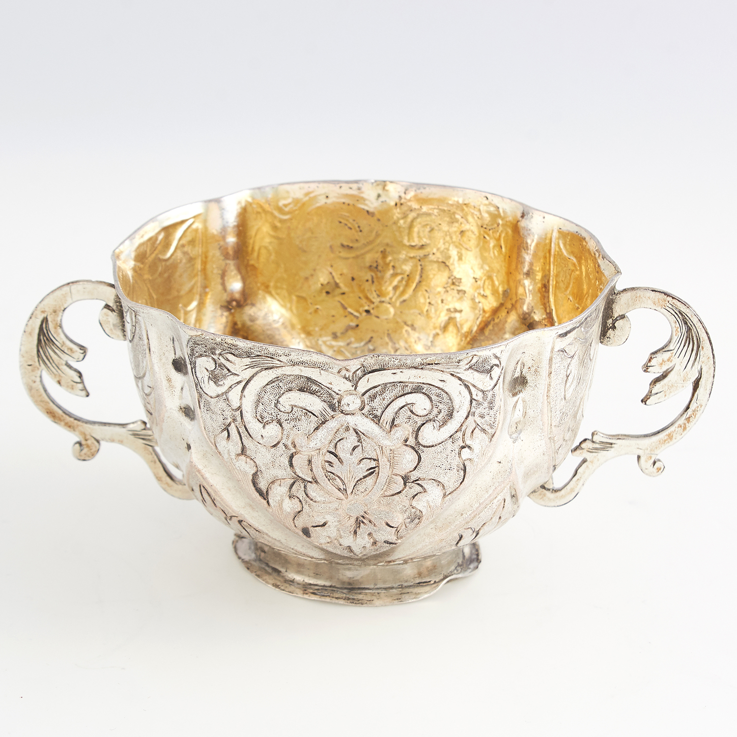 Los 60 - ANTIQUE GERMAN SILVER PORRINGER of rounded form with chased foliate scroll decoration, twin