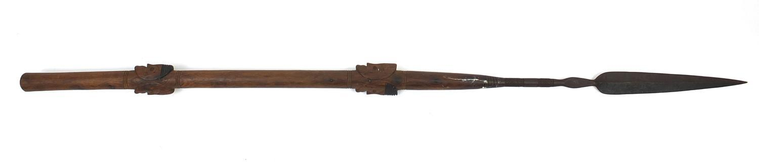 Lot 328 - African hardwood ceremonial spear carved in relief with face masks, 208cm long : For Further