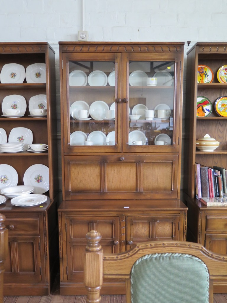 Lot 1 - A pair of Ercol dark oak bookcase cabinet, each with open shelves over two short drawers and
