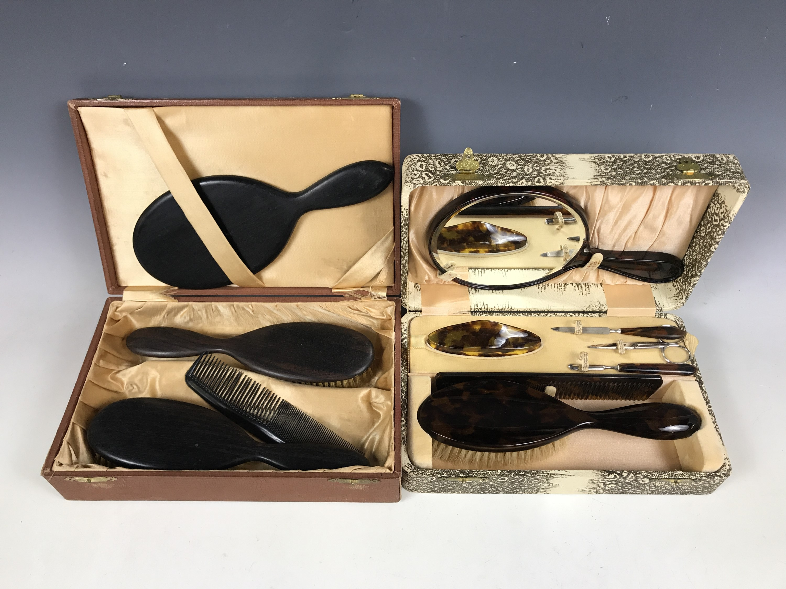 Lot 10 - A cased grooming set comprising hairbrush and manicure items, together with one further cased