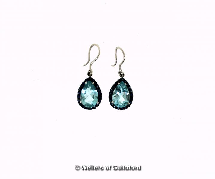Lot 5104 - *Pair of blue topaz and sapphire drop earrings, a pear shaped blue topaz with a surround of round
