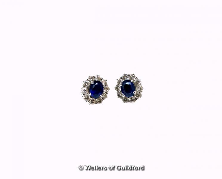 Lot 5109 - Sapphire and diamond cluster earrings, each earring set with an oval cut sapphire with a surround of