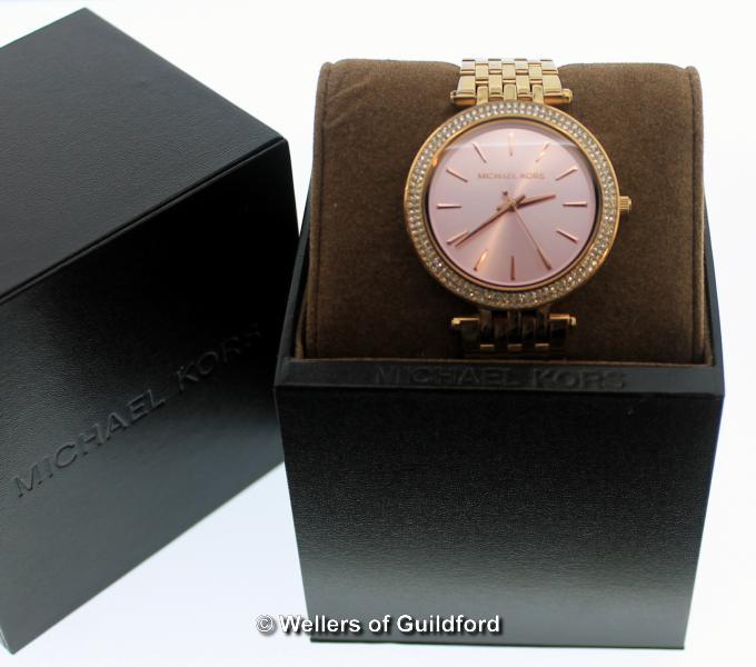 Lot 5050 - *Ladies' Michael Kors wristwatch, circular pink dial with white stone set bezel, baton hour markers,