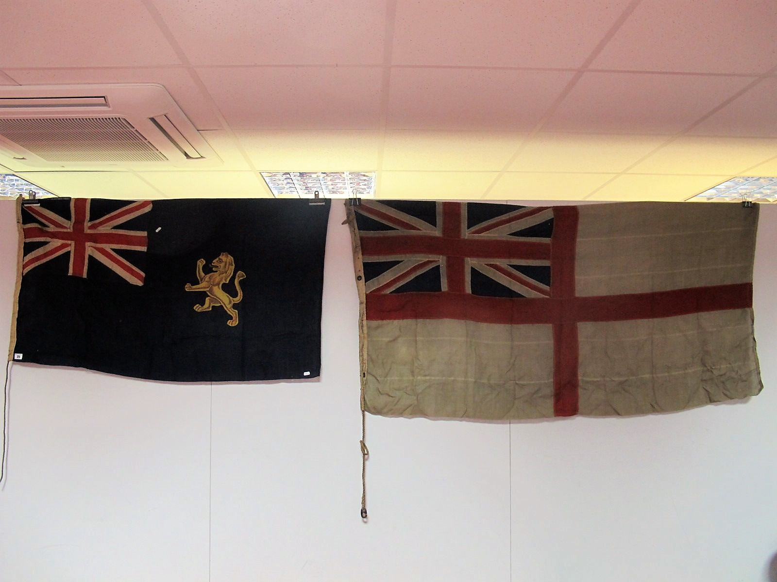Lot 25 - A Royal Navy White Ensign, 87 x 170cm, and a blue ensign with golden lion, 75cm by 130cm.